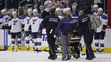 Winnipeg Jets' Jacob Trouba (8) is taken off the ice by paramedics after crashing head first into the boards during second period NHL action against the St. Louis Blues in Winnipeg on Friday, October 18, 2013. (JOHN WOODS/THE CANADIAN PRESS)