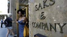 Shoppers use a Fifth Avenue entrance to Saks, in New York, on July 29, 2013. With its purchase of Saks Inc., Hudson's Bay Co. is picking up a storied American brand with an international following and a reputation for luxury retailing that goes back nearly a century. (Richard Drew/AP)