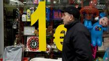 A Kosovo Albanian walks by a lower price shop in Pristina on December 26, 2011. (ARMEND NIMANI/AFP/Getty Images/ARMEND NIMANI/AFP/Getty Images)