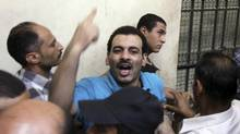 A defendant reacts as he and other defendants are led behind bars to hear the ruling on their case for sexual harassment at a court in Cairo on July 16, 2014. (AL YOUM AL SAABI/REUTERS)