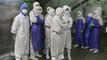 Employees stand during a seizure conducted by officers from the Shanghai Food and Drug Administration, at the Husi Food factory in Shanghai, July 20, 2014. (REUTERS)