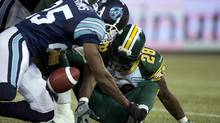 Toronto Argonauts defensive back Pat Watkins (25) dives for a fumble by Edmonton Eskimos running back Cory Boyd (28) during first half CFL Eastern Semi-Final action in Toronto on Sunday November 11, 2012. (Frank Gunn/THE CANADIAN PRESS)