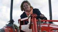 Ontario NDP Leader Andrea Horwath gets behind the wheel of a tractor during a campaign stop at the International Plowing Match in Chute-a-Blondeau on Sept. 20, 2011. (Adrian Wyld/THE CANADIAN PRESS)