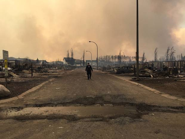 In this image released by the Alberta RCMP on May 5, 2016, a police officer walks on a road past burned down houses in Fort McMurray, Alberta.