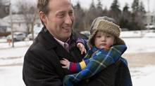 Justice Minister Peter MacKay carries his son Kian as they arrive at Fairview Junior High School in Halifax on Thursday, Jan. 9, 2014. (Andrew Vaughan/THE CANADIAN PRESS)