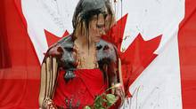 A protester sits in front of a Canadian flag as she is doused in molasses during an anti-Alberta-oil-sands protest on Parliament Hill on Sept. 8, 2010. (Adrian Wyld/The Canadian Press)