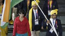 India's flag bearer Sushil Kumar holds the national flag as he leads the contingent in the athletes parade during the opening ceremony of the London 2012 Olympic Games at the Olympic Stadium July 27, 2012. A mystery woman gatecrashed India's march past at the Olympic opening ceremony and the delegation are seeking an apology from the London organisers, an Indian newspaper reported on Sunday. Photographs show a woman in red and blue walking close to Kumar on Friday night, in complete contrast to female members of the contingent who were wearing yellow sarees and blue blazers. (Max Fossi/Reuters)