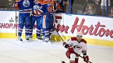 Carolina Hurricanes' Andrej Sekera (4) watches as Edmonton Oilers' Taylor Hall (4), Jordan Eberle (14) and Sam Gagner (89) celebrate the game winning goal during overtime NHL action in Edmonton, Alta., on Tuesday, December 10, 2013. (JASON FRANSON/THE CANADIAN PRESS)
