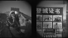 Students who visit the Badaling section, left, pose for a portrait photographer who works at the Great Wall; right, samples and prices of the photographer's work. (John Lehmann/The Globe and Mail)