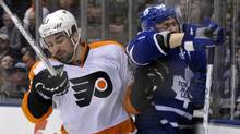 Toronto Maple Leafs forward Mikhail Grabovski is hit into the boards by Philadelphia Flyers defenceman Marc-Andre Bourdon (L) during the second period of their NHL hockey game in Toronto March 29, 2012. (MIKE CASSESE/REUTERS)
