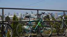 Bicycles rest against a railing overlooking the downtown skyline in Vancouver, British Columbia, Friday, July 19, 2013. (Rafal Gerszak For The Globe and Mail)
