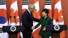 Prime Minister Stephen Harper, left, shakes hands with South Korean President Park Geun-hye during joint press conference after their meeting at the presidential Blue House in Seoul, Tuesday, March 11, 2014. (Lee Jin-man/AP Photo)