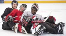 Team Canada teammates Dougie Hamilton, left, Anthony Camara, centre, and Malcolm Subban, right, ham it up for the cameras, pretending to bobsleigh during practice at the IIHF World Junior Championships in Ufa, Russia on Saturday, Dec. 29, 2012. Far from home, the Canadian team sticks together on and off the ice at world juniors. (Nathan Denette/THE CANADIAN PRESS)