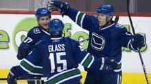Vancouver Canucks' Rick Rypien, left, celebrates his goal against the New York Rangers with teammates Tanner Glass and Christian Ehrhoff during third period NHL hockey in Vancouver, British Columbia November 3, 2009. (ANDY CLARK)