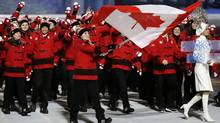 Hayley Wickenheiser of Canada carries the national flag as she leads the team during the opening ceremony of the 2014 Winter Olympics in Sochi, Russia, Friday, Feb. 7, 2014. (Mark Humphrey/Associated Press)