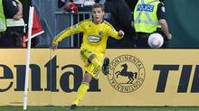 Columbus Crew midfielder Robbie Rogers kicks a corner kick as Toronto FC fans wave flags to protest next year's ticket prices during second half MLS soccer action in Toronto on Saturday, October 16, 2010. (Reuters)