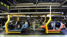 An employee works on a Citroen C3 Picasso on a production line at the PSA Peugeot Citroen Slovakia plant in Trnava. (© Radovan Stoklasa / Reuters/REUTERS)