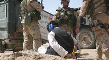 Soldiers supervise a detainee during Operation Medusa in the Panjwaii district of Kandahar Province, Afghanistan. (Les Perreaux/Canadian Press)