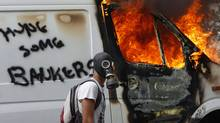 A protester wearing a gas mask walks beside a burning van during violent protests against austerity measures in Athens, June 28, 2011. (Yannis Behrakis/Reuters/Yannis Behrakis/Reuters)