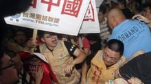 Supporters and protesters of Zhang Zhijun, minister of Beijing's Taiwan Affairs Office, fight on his arrival at airport in Taoyuan county, Taiwan, Wednesday, June 25, 2014. (Chiang Ying-ying/AP)