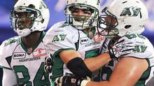 Saskatchewan Roughriders Weston Dressler, centre, celebrates a touchdown against the Toronto Argonauts with Chris Best, right, and Greg Carr, left, during second half CFL action in Toronto on Monday, October 8, 2012. (Aaron Vincent Elkaim/THE CANADIAN PRESS)