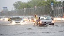 A woman gets gets out of her car to check it in flood water on Lakeshore West during a storm in Toronto on Monday, July 8, 2013. (FRANK GUNN/THE CANADIAN PRESS)