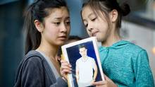 Sixteen-year-old Tracey Phan, left, watches as her nine-year-old sister Angela Phan, holds a photo of their father Michael Phan, who was left brain damaged after being injured on a Langley mushroom farm in 2008, while attending a coroner's inquest into the 2008 deaths and injuries on the farm, in Burnaby, B.C.. (Darryl Dyck for The Globe and Mail/Darryl Dyck for The Globe and Mail)