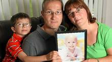 Bryan and Joanne Bedard, with their seven-year-old son Bryan, hold a picture of their daughter Katelyn, who died in 2005 of acute myeloid leukemia. (Dave Chidley For The Globe and Mail)