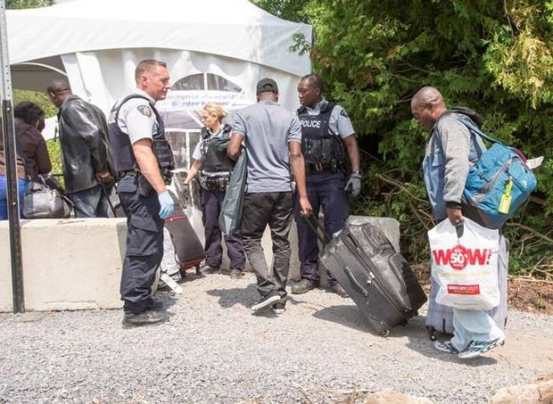 A group of asylum seekers cross the Canadian border at Champlain, N.Y., Friday, August 4, 2017.