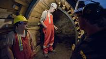 The Edmonton city workers responsible for discovering dinosaur fossils during a sewer tunnel excavation, Ryley Paul, left, and Aaron Krywiak, centre, check out the underground site on Aug. 23, 2010. (John Ulan/John Ulan/The Canadian Press)