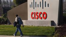 A pedestrian walks past the Cisco logo at the technology company's campus in San Jose, California on Feb. 3, 2010. (Robert Galbraith/Reuters)
