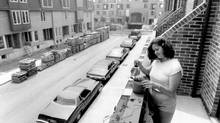 New resident Sina Mitolidis waters the plants on the balcony of her St. Lawrence home, 1979. (Edward Regan/The Globe and Mail)
