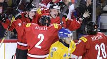 Switzerland's Joel Vermin (L), Cedric Hachler (2), Tanner Richard and Christoph Bertschy celebrate a goal during the second period of play against Sweden at the 2012 IIHF U20 World Junior Hockey Championship in Calgary, Alberta, December 28, 2011. (STRINGER/CANADA/REUTERS)