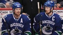 Daniel Sedin, left, and his twin brother Henrik Sedin, both of Sweden, sit on the bench during the third period of game 5 of an NHL Western Conference quarterfinal Stanley Cup playoff hockey series in Vancouver, B.C., on Thursday April 21, 2011. (DARRYL DYCK)