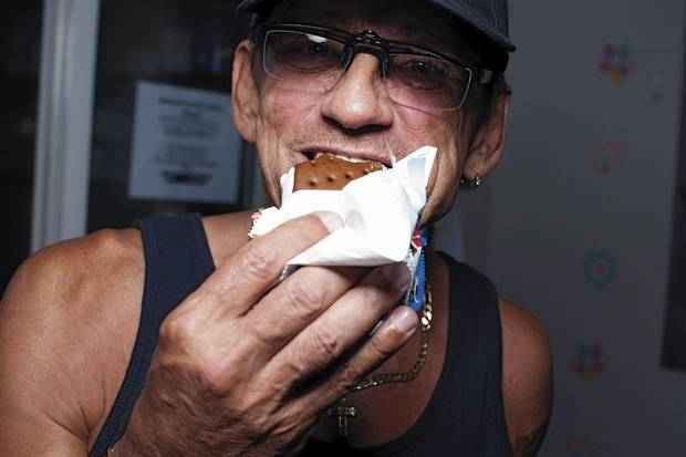 Richard Teague, a club facilitator, polishes off an ice cream sandwich.