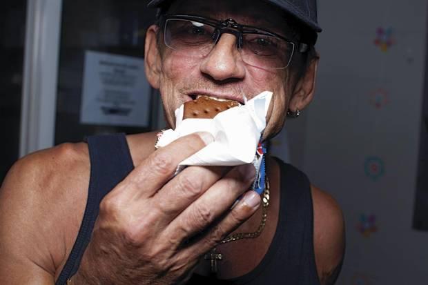 Richard Teague, a club facilitator, polishes off an ice cream sandwich.