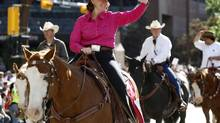 Alberta Premier Alison Redford waves to the crowd as she rides a horse during the Calgary Stampede parade in Calgary, Friday, July 5, 2013. This is the 101st edition of the Stamepde which continues until July 14. (Jeff McIntosh/THE CANADIAN PRESS)