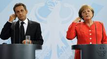 French President Nicolas Sarkozy (L) and German Chancellor Angela Merkel adjust their earpieces as they address a news conference at the Chancellery in Berlin June 17, 2011. (© Fabrizio Bensch / Reuters/REUTERS)
