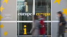 People walk in front of an information office outside of an EU summit in Brussels on Thursday, Nov. 22. Leaders from around Europe are arriving in Brussels on Thursday for what promises to be a turbulent summit on the budget for the 27-country European Union. (Virginia Mayo/Associated Press)
