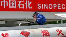 A Chinese worker checks a fuel tank at a Sinopec petrol station in Beijing, 26 April 2007. (TEH ENG KOON/AFP/Getty Images)