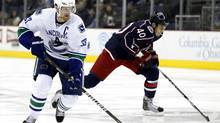 Vancouver Canucks' Henrik Sedin (33) takes the puck past Columbus Blue Jackets' Jared Boll (40) during the first period of their NHL hockey game in Columbus, Ohio December 23, 2010. (MATT SULLIVAN)