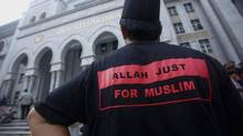 """A Muslim man stands outside the court in Putrajaya outside Kuala Lumpur June 23, 2014. Malaysia's Federal Court on Monday rejected an application for leave by the Catholic Church to challenge a Court of Appeal decision to prohibit the weekly Herald Bahasa Malaysia section from using the word """"Allah"""". (SAMSUL SAID/REUTERS)"""
