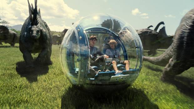 Zach (Nick Robinson) and Gray (Ty Simpkins) roam among the dinosaurs in a scene from Jurassic World.