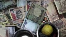 In this photo taken on Nov. 17, 2010, Indian Rupee notes of different denomination lie inside the cash counter of a retail shop in Mumbai, India. (Rajanish Kakade/Rajanish Kakade/AP)