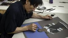 In this file photo Itee Pootoogook works on a drawing of a woman wearing a traditional caribou hide amauti. (William Ritchie)