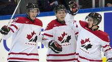 Team Canada forward Anthony Mantha (left) is congratulated by teammates Curtis Lazar (centre) and Nic Petan (right) after scoring on Germany during second period qualification round IIHF World Junior Hockey Championships in Malmo, Sweden on Thursday December 26, 2013. (CP)