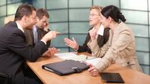 Business people arguing at a table. From photos.com (Marcin Balcerzak/Getty Images)