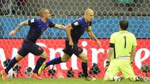 Netherlands' Arjen Robben, centre, celebrates with teammate Wesley Sneijder after scoring his sides fifth goal during the group B World Cup soccer match between Spain and the Netherlands at the Arena Ponte Nova in Salvador, Brazil, Friday, June 13, 2014. (Associated Press)