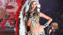 This Nov. 7, 2012 photo released by Starpix shows model Karlie Kloss wearing an Indian headdress during the taping of The 2012 Victoria's Secret Fashion Show in New York. (Amanda Schwab/AP)
