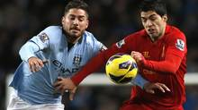Manchester City's Javi Garcia (L) challenges Liverpool's Luis Suarez during their English Premier League soccer match at the Etihad Stadium in Manchester, northern England February 3, 2013. (PHIL NOBLE/REUTERS)
